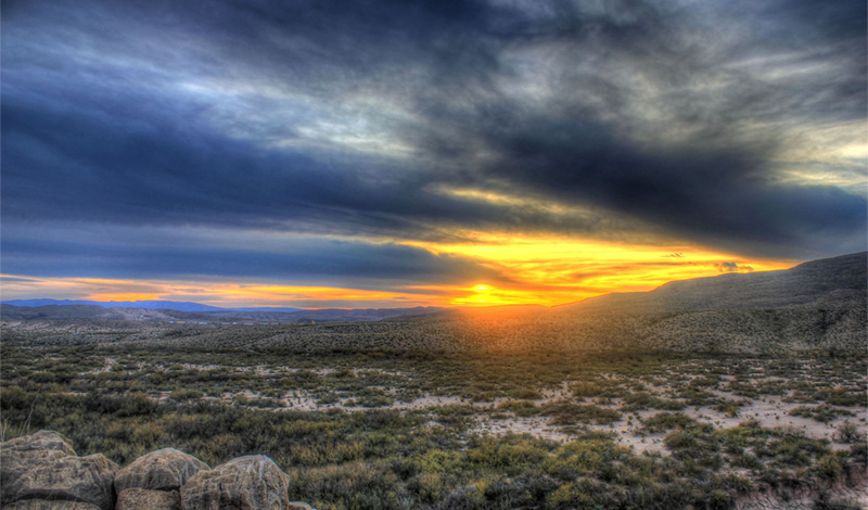 The sun sets behind the hills from Boquillas Canyon, Big Bend State Park, Texas. Photo by Archbob / Wikimedia.